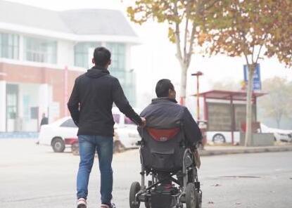 大学生带瘫痪父亲上学:已带6年 考研也要带上他